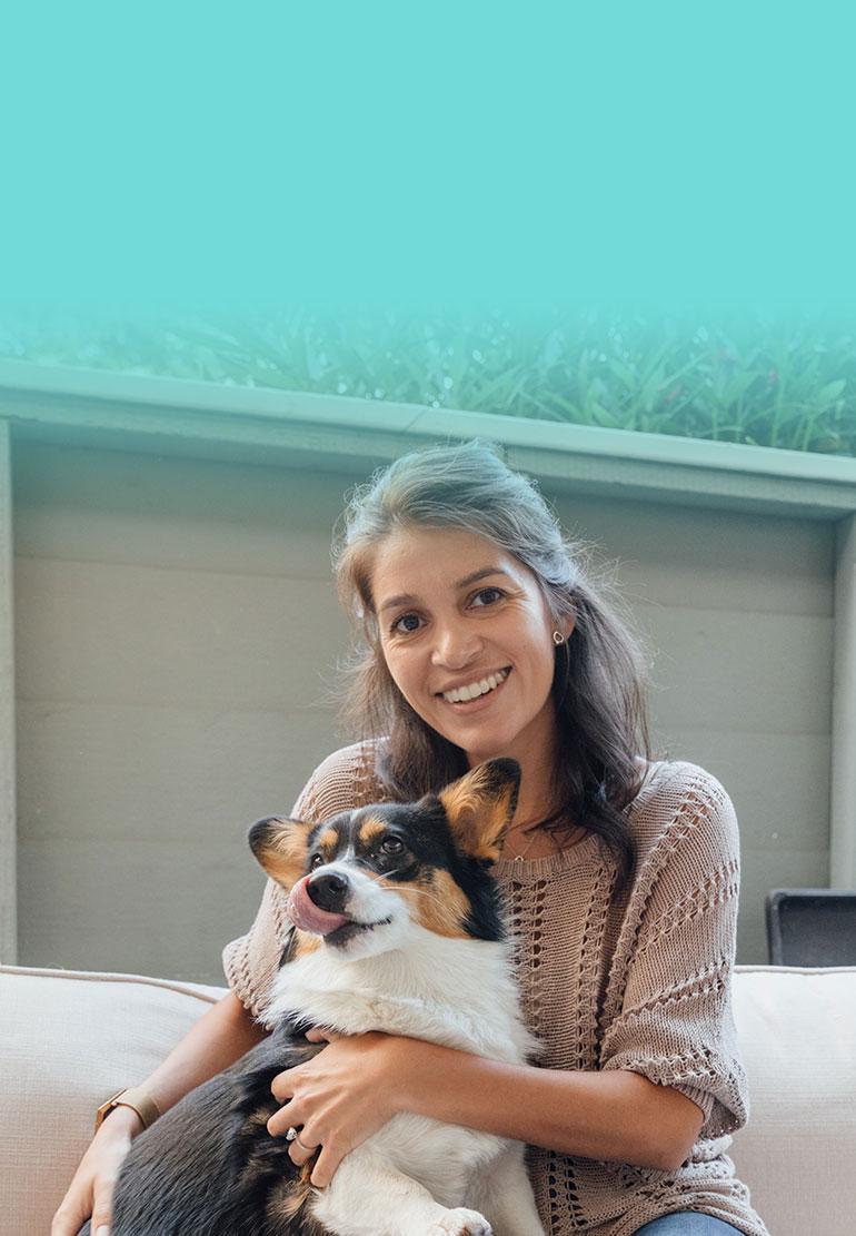 A women smiles while holding a Corgi.