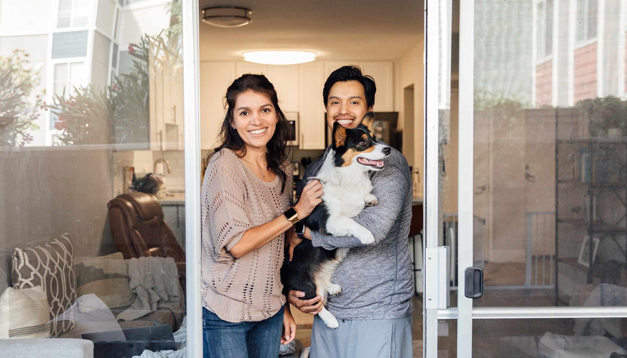 A women smiles and stands close to a man who is holding a Corgi.