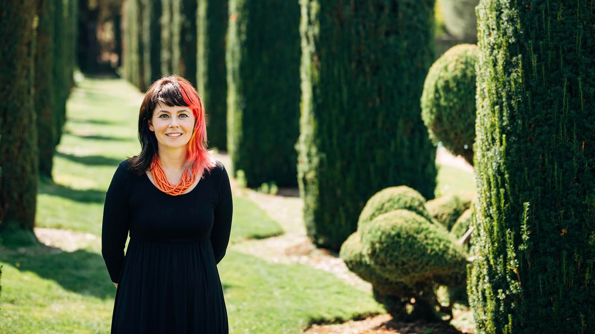 A women with pink and black hair smiles with her hands behind her back. Columns of greenery are behind her.