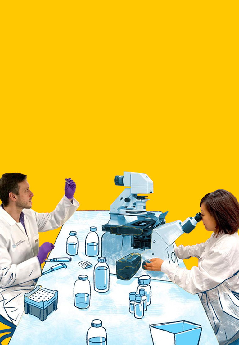 Two scientists work at a lab table and look at samples.