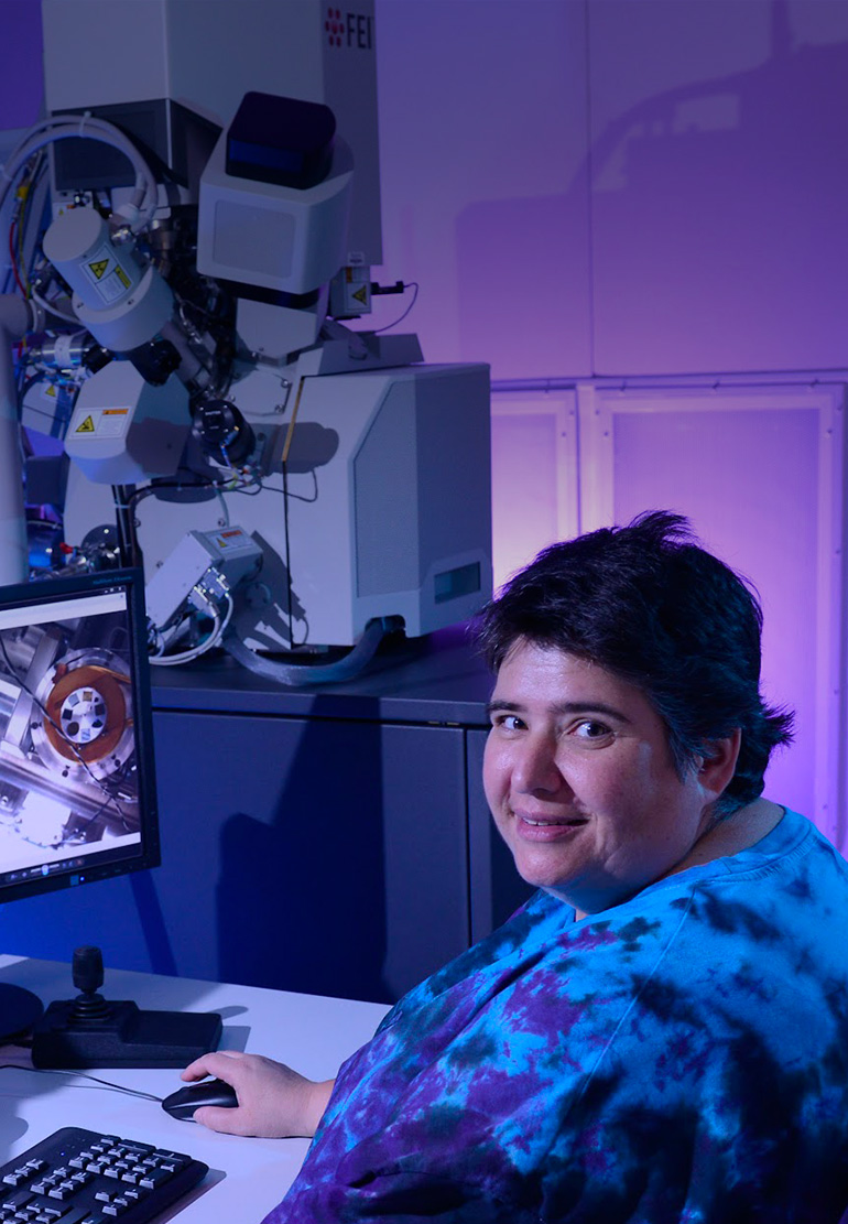 A women looks at the camera and smiles as she work at two monitors in a blue-lit room.