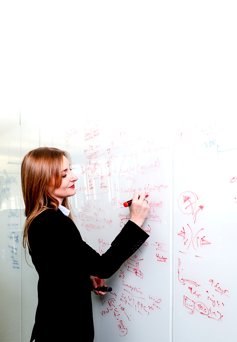 A women writes equations on a white board.