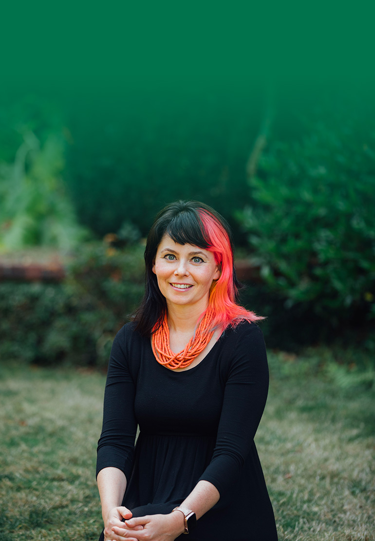 A women with black and pink hair smiles with greenery behind her.