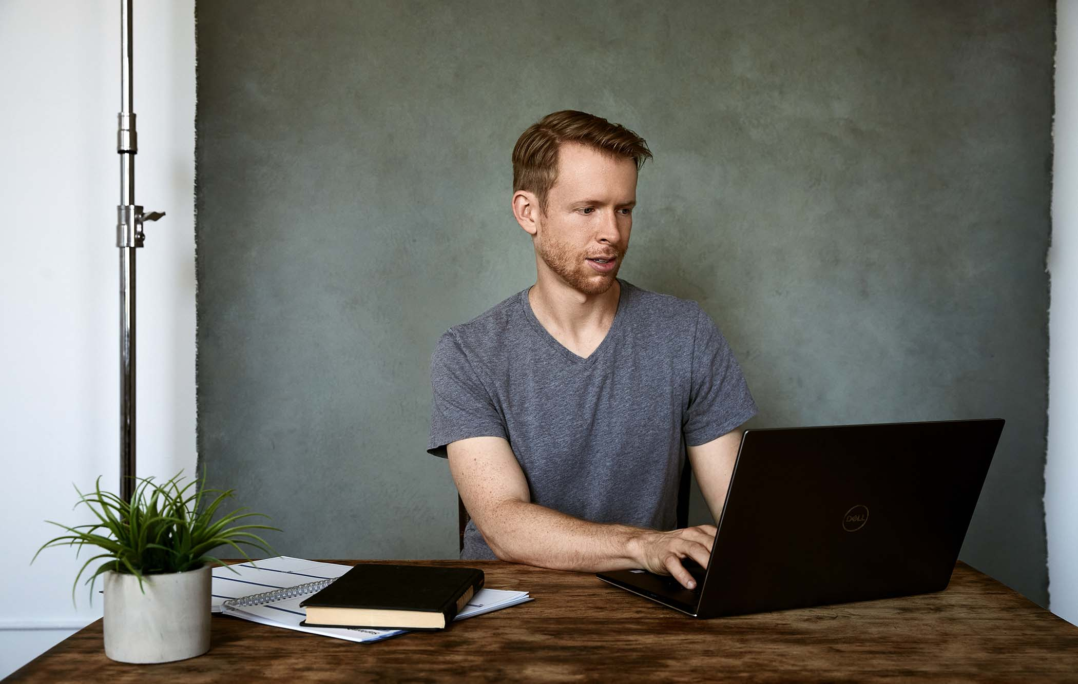 A man works on a computer at a desk.