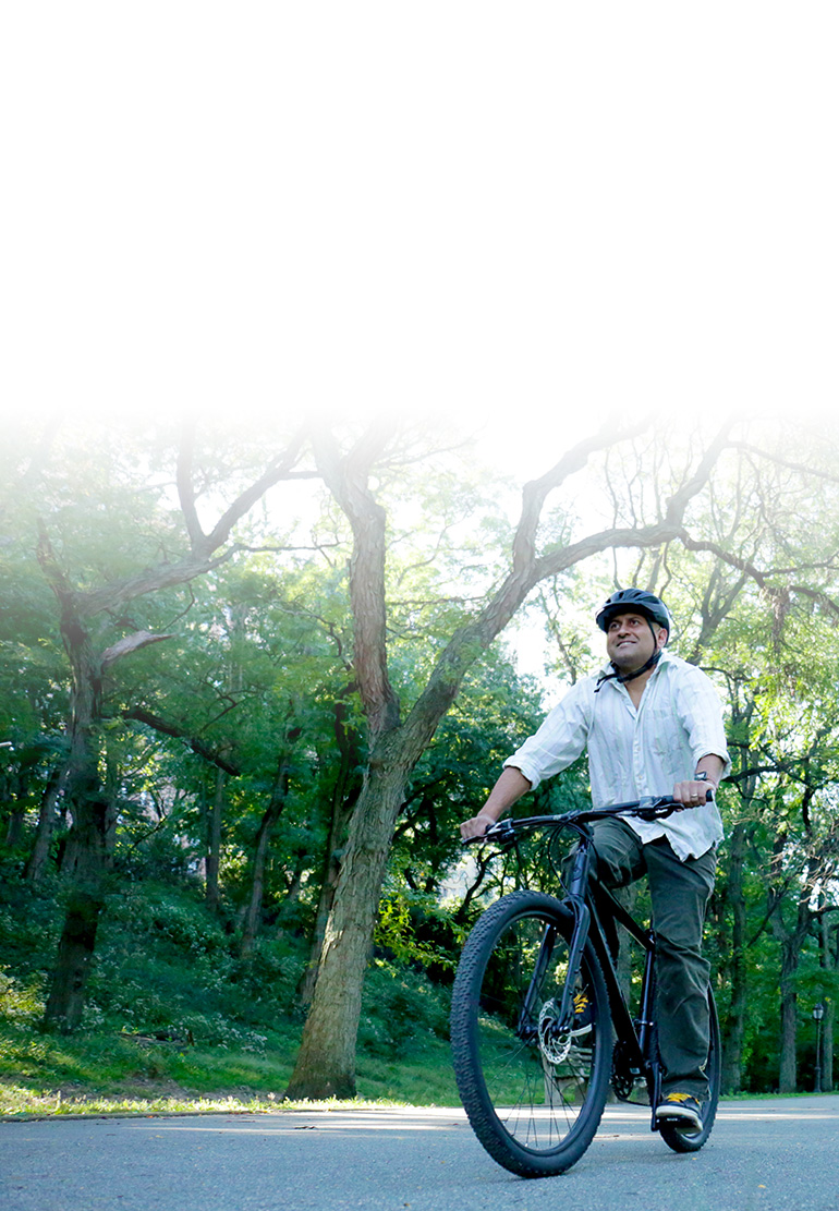 A man rides a bike wearing a helmet. Green trees are in the background.