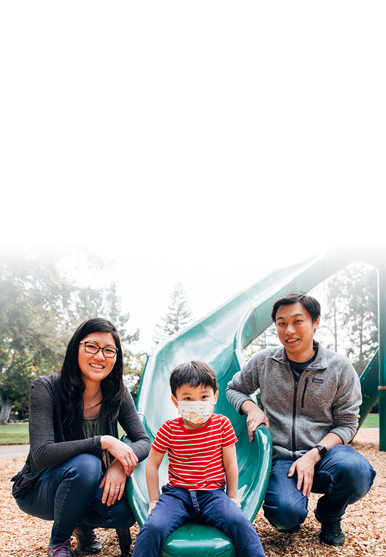 A women, child and man pose for a family picture at the foot of a playground slide.