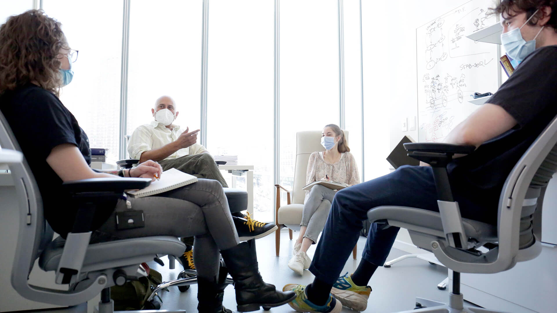 A group of people wearing masks sit in a circle in an office.