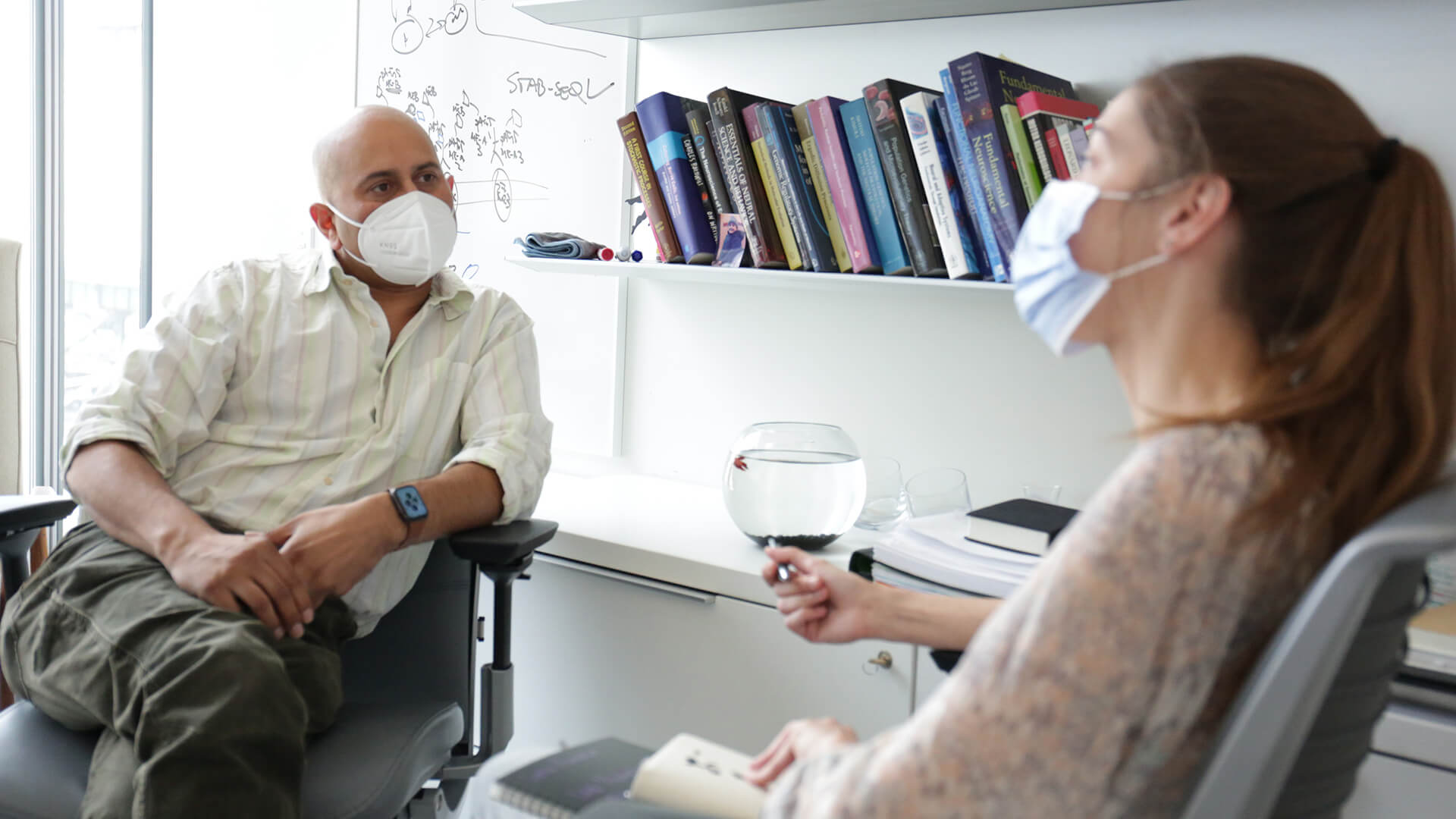 A man and woman wearing masks sit in an office chatting.