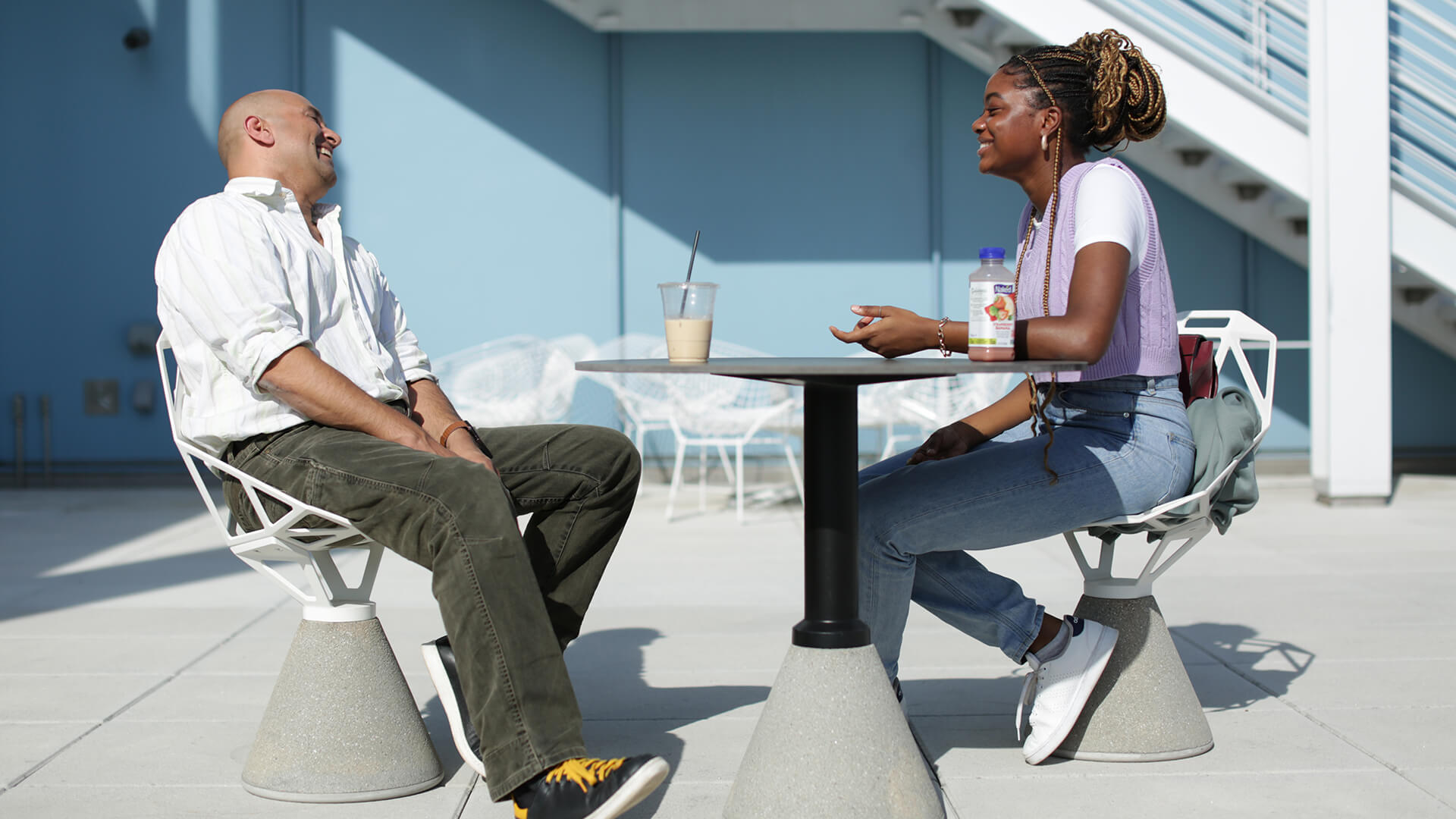 A man and woman sit outside chatting. The man is laughing.