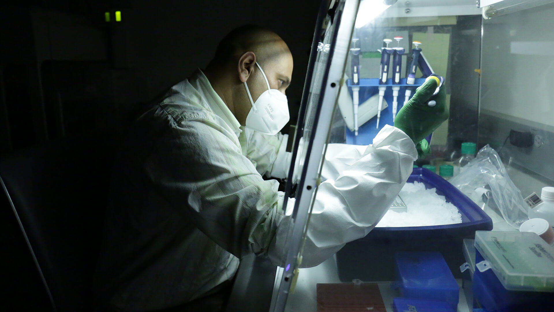 A man in white protective clothing works on a machine in a lab.