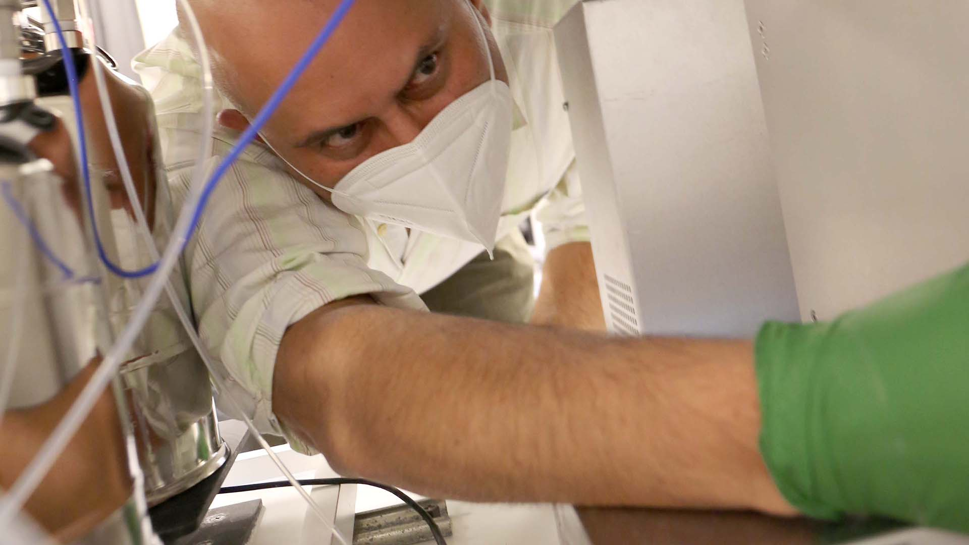 A man wearing a mask works to fix a machine in a lab. A blue wire hangs in front of his face.